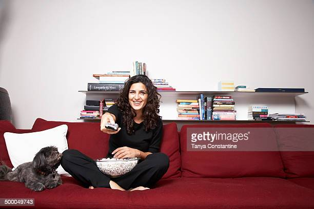 Middle Eastern woman watching television on sofa