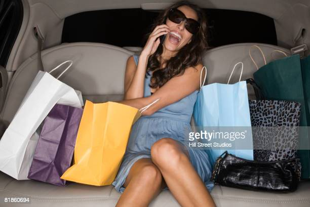 Middle Eastern woman with shopping bags in limousine