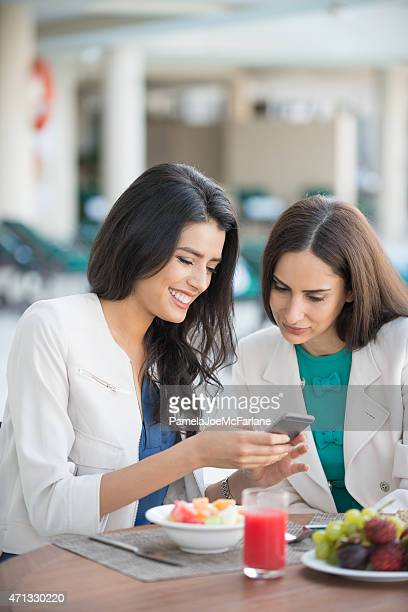 Middle Eastern Women Friends Looking at Cellphone While Having Lunch