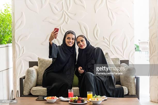 Mujeres del Medio Oriente en Abayas posando para Selfie durante el almuerzo