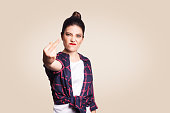 Middle finger sign. Unhappy angry young woman showing middle finger with unsatisfied face. studio shot on beige background. focus on face.