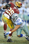 Middle linebacker DeVonte Holloman of the Dallas Cowboys puts a hit running back Roy Helu of the Washington Redskins running with the ball in the...