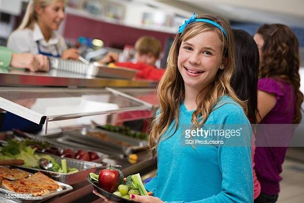 Middle school girl with students in cafeteria lunch line