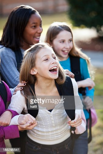 Middle school girls with bookbags outside