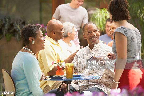 Middle-aged African couple paying check at restaurant
