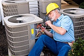 Middle-aged Air Conditioning Repairman At Work
