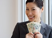 Middle-aged Asian businesswoman holding yen banknotes