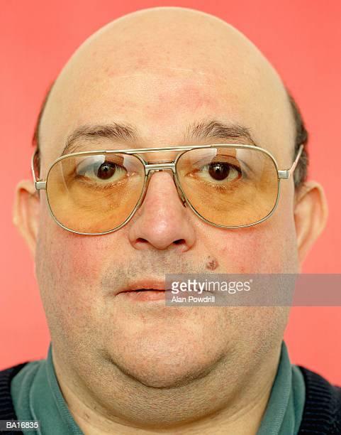 Middle-aged bald man wearing glasses, close-up, studio portrait