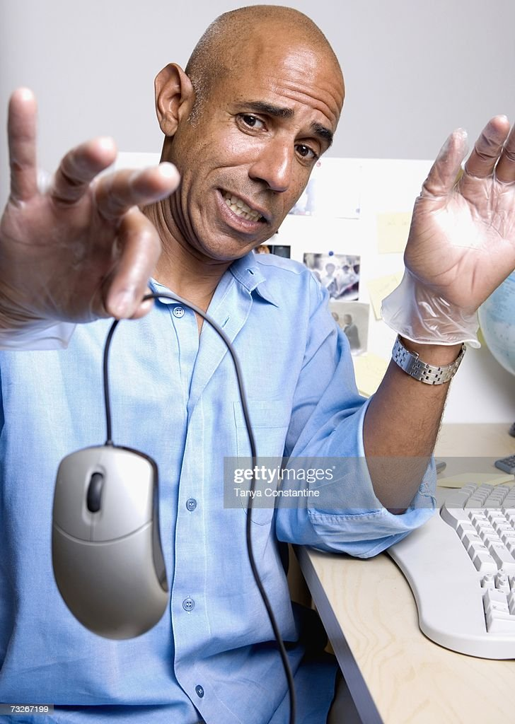 Middle-aged businessman holding out computer mouse at desk : Stock Photo