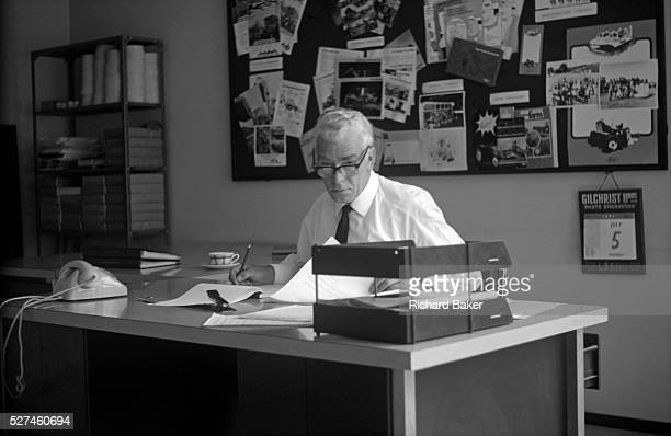 A middleaged businessman looks up from paperwork during a working day in his 1970s Brussels office The executive wearing a white shirt and tie pauses...