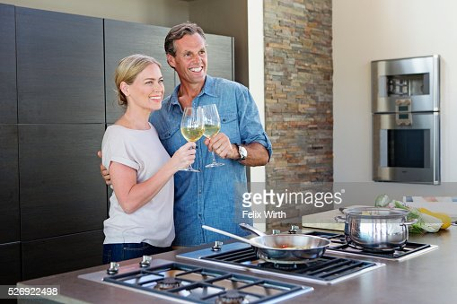Middle-aged couple cooking together and drinking wine : Stock-Foto