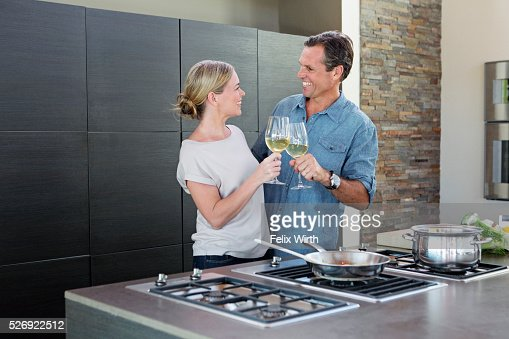 Middle-aged couple cooking together and drinking wine : Stock Photo
