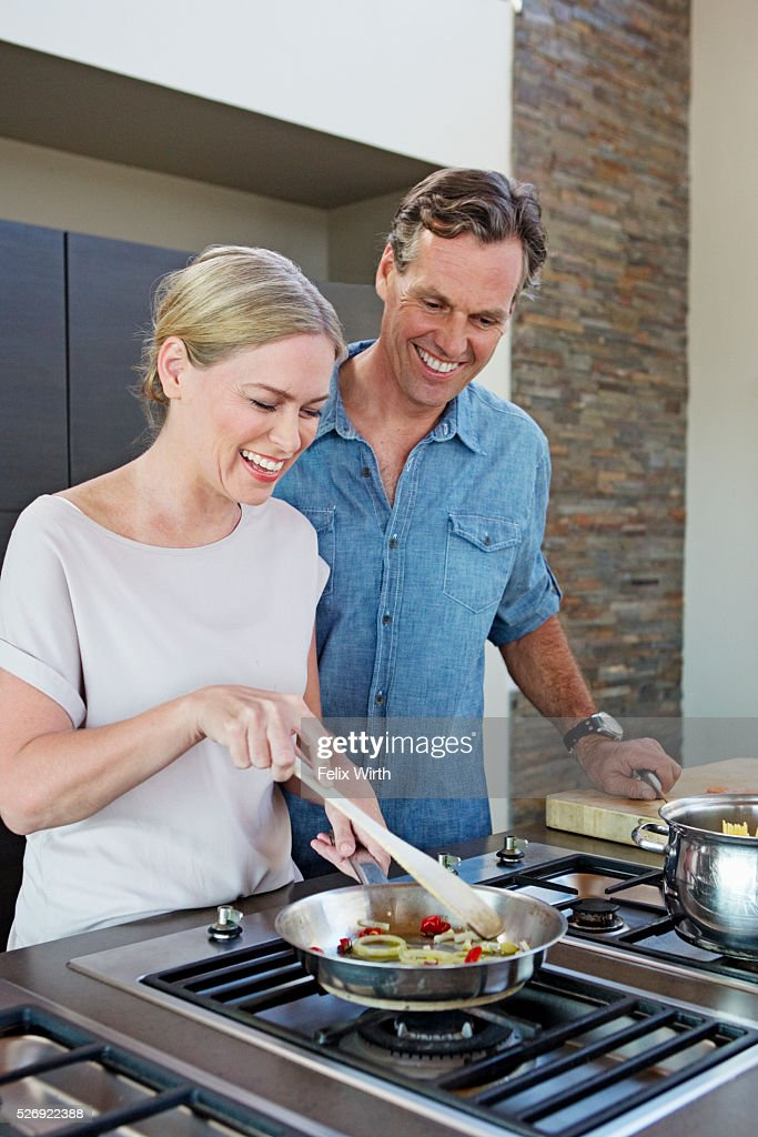 Middle-aged couple cooking together : Stock Photo