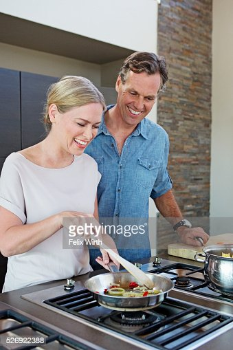 Middle-aged couple cooking together : Bildbanksbilder