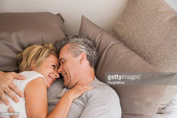 Middle-aged couple cuddling in bed