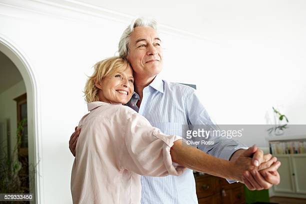 Middle-aged couple dancing and smiling