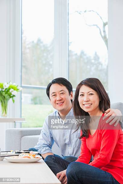 Middle-aged couple eating at coffee table