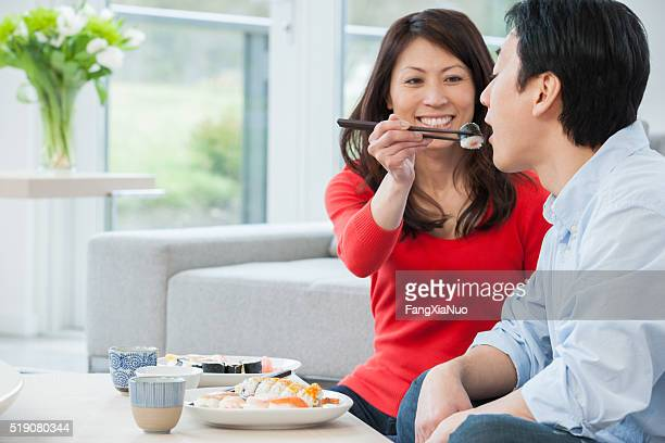 Middle-aged couple feeding each other sushi