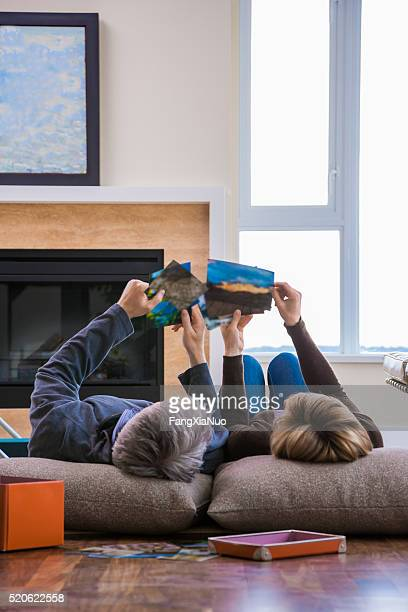 Middle-aged couple on floor looking at photographs