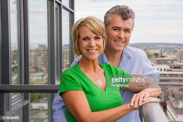 Middle-aged couple standing on balcony