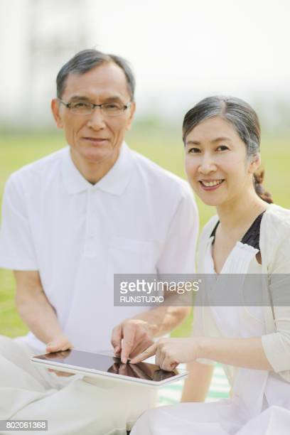 Middle-aged couple using digital tablet in park