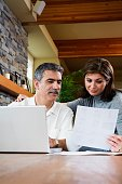 Middle-aged couple using laptop indoors