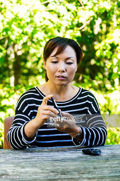 Middle-aged diabetic woman of Asian descent checking her blood