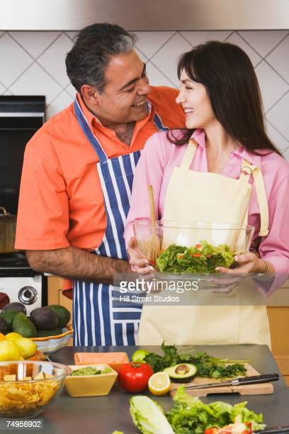 Middle-aged Hispanic couple hugging in kitchen