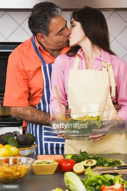 Middle-aged Hispanic couple kissing in kitchen