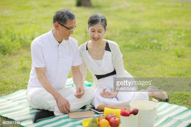 middle-aged man and a woman enjoying a picnic at a park
