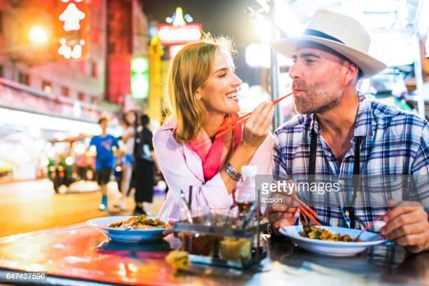 Homme d'âge moyen et sa Dame blonde beau compagnon dans le quartier chinois de Bangkok