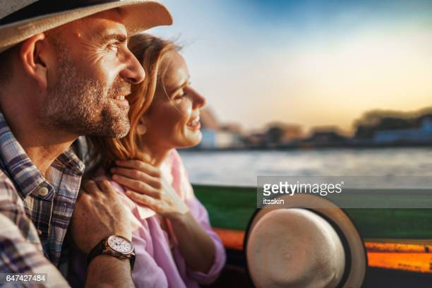Middle-aged man and his companion handsome blond lady on a boat ride in Bangkok