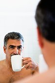 Middle-aged man drinking coffee and looking in mirror