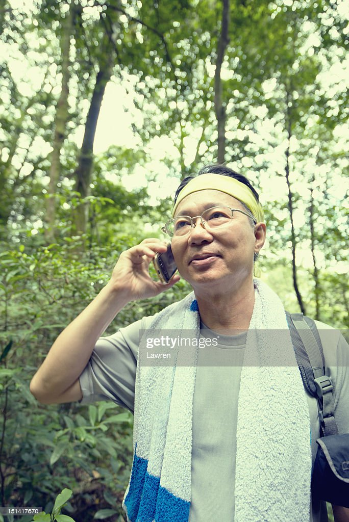 Middle-aged man hiking and talking on phone : Stock Photo