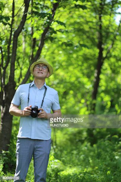 Middle-aged man holding a camera in the woods