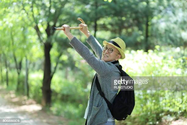 middle-aged man holding a cane is laughing at the camera