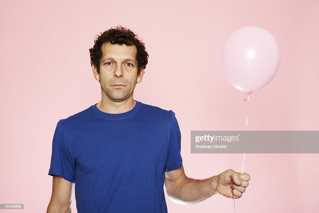 A middle-aged man holding a pink balloon. : Stock Photo