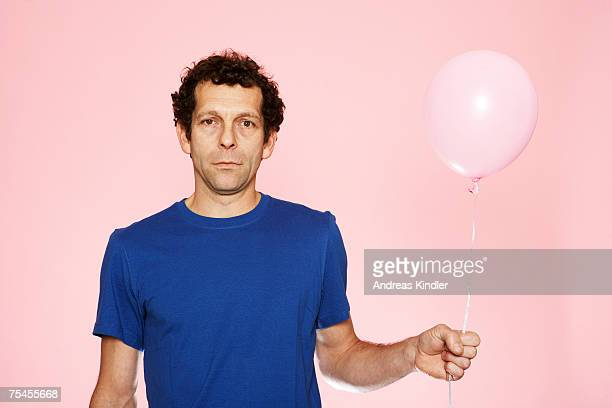 A middle-aged man holding a pink balloon.
