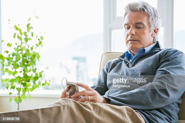 Middle-aged man listening to MP3 player