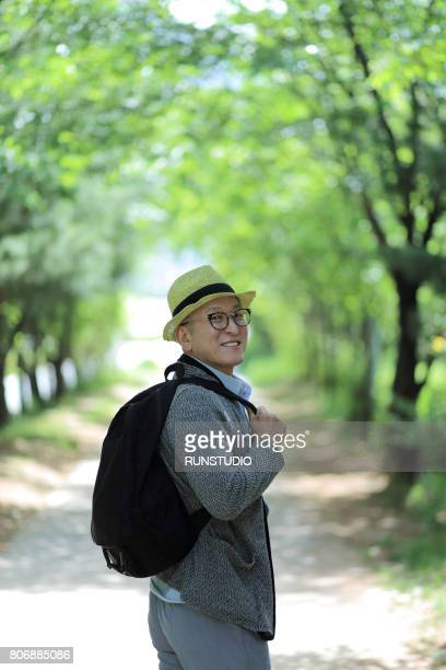 middle-aged man looking around behind while walking