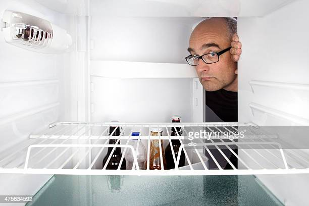 Middle-aged man opens a fridge