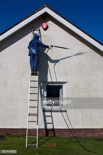 A middleaged man power washes the white render on the exterior of his bungalow home In strong sunshine we see the gentleman up a ladder leaning...