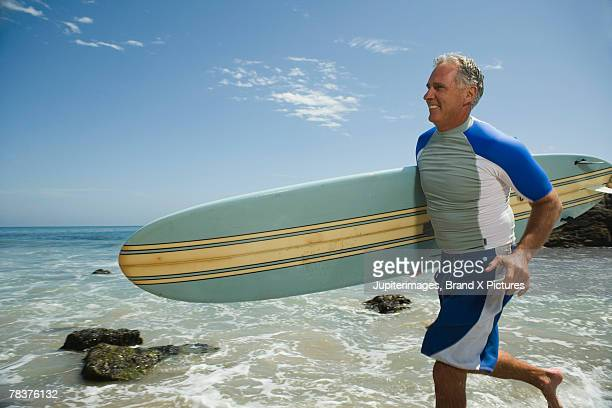 Middle-aged man running with surfboard