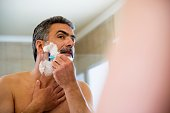 Middle-aged man shaving face