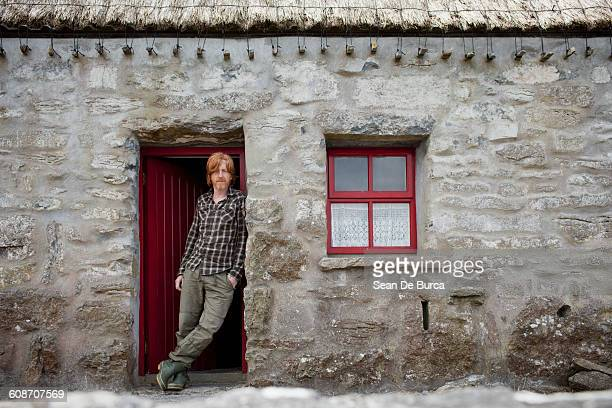 Middle-aged man standing by front door of house