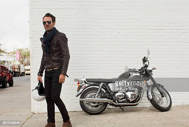 Middle-aged man standing next to his motorcycle