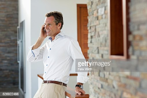Middle-aged man talking on phone at home : Stock Photo