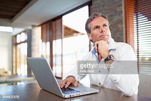 Middle-aged man using laptop at home : Stock-Foto