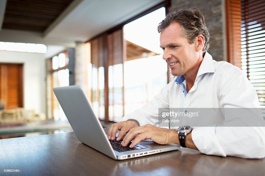 Middle-aged man using laptop at home : Foto de stock