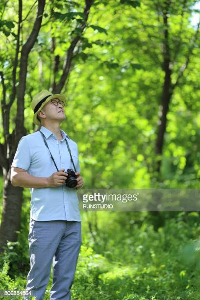 Middle-aged man walking with camera